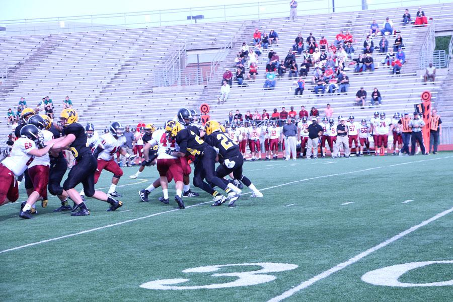 The football team tries to sneak the ball past the 35 yard line.