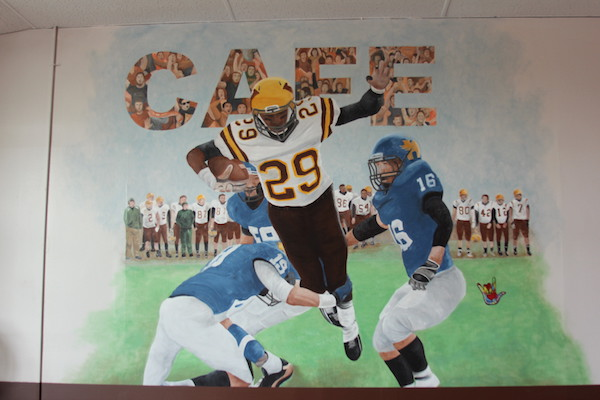 A mural in Cafe 29 depicts Andre in the state championship game against Hutchinson in 2012. Photo by Kelsea Lilla.