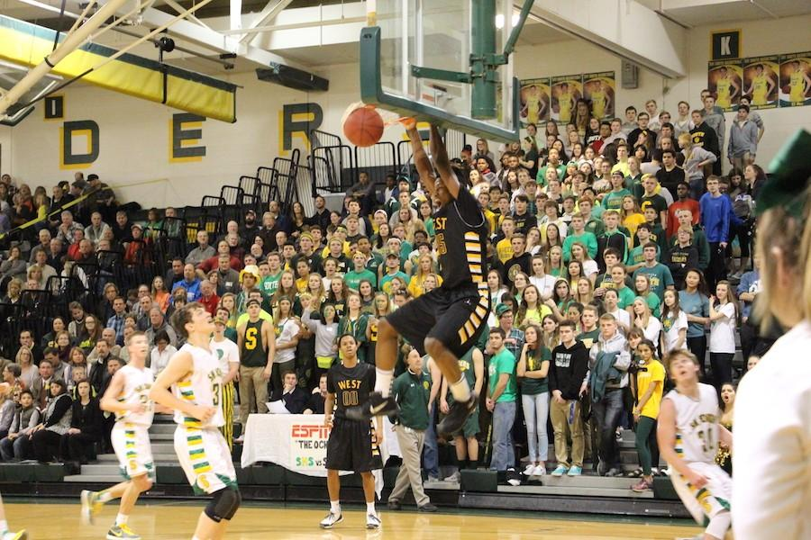 Senior Darrell Stewart hangs on the rim after a dunk.