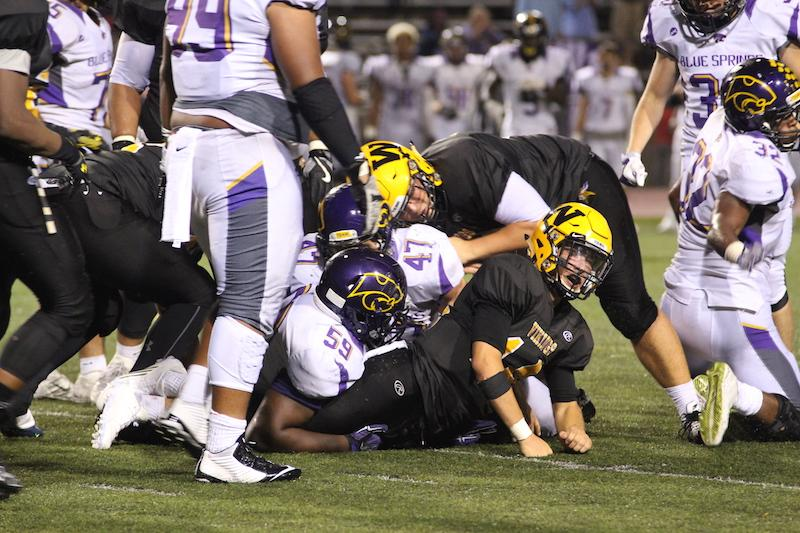 Zach Witters struggles under pile of Blue Springs players (Mikaela Kelly-Price)