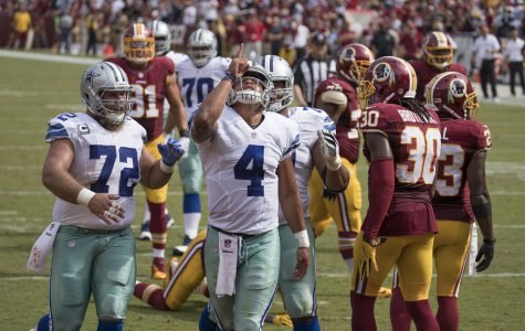Quarterback Dak Prescott points to the sky in celebration after a nice play.