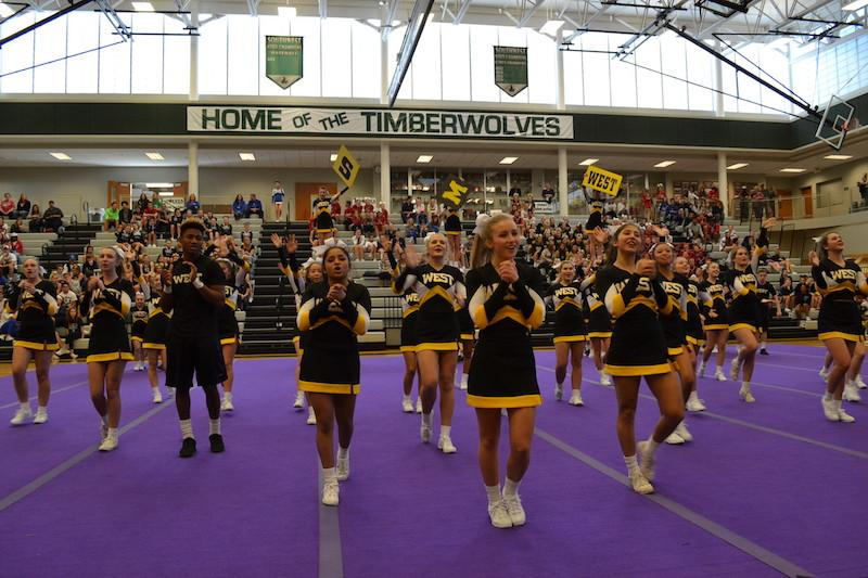 The cheer squad performs their opening chant in front of a large crowd