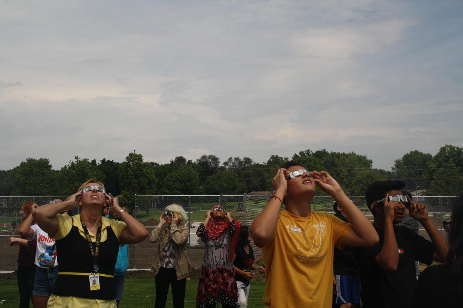 Students and faculty look towards the eclipse with their special glasses.
