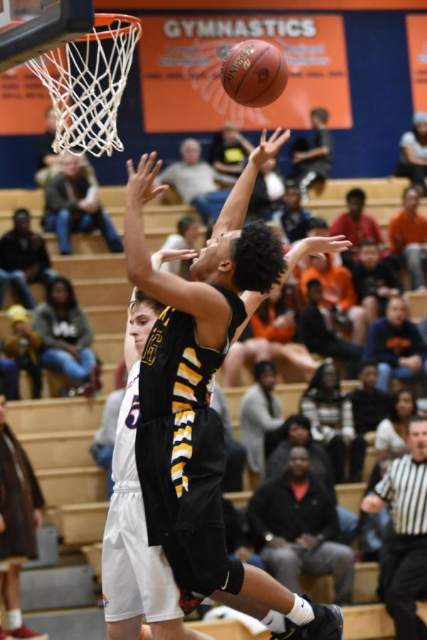 Junior Eric Rhymes completes a layup vs Olathe East, Varsity, December 1