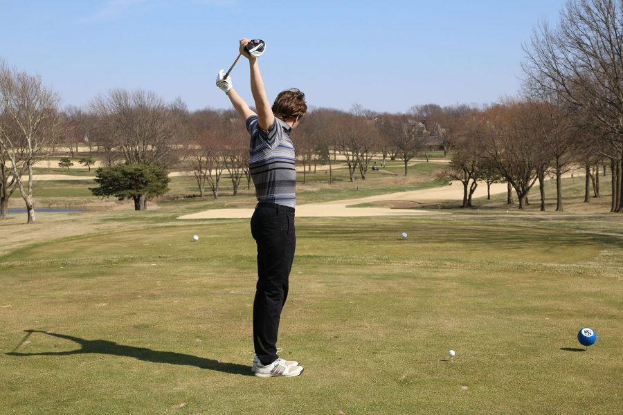 4 year team member, Sam Weiss, stretches at the beginning of the round to prepare to hit his tee shot.