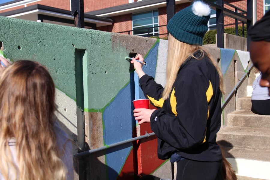 Madeline Meyer paints the wall with green paint at beautification.