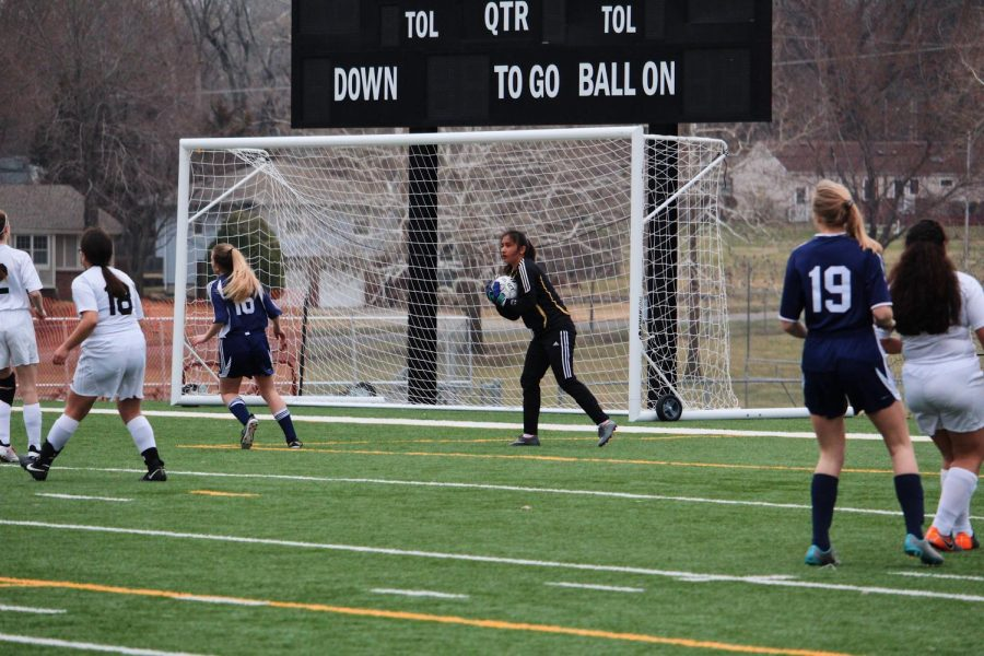 Goalie Lili Varela scoops up the ball just before it goes in.