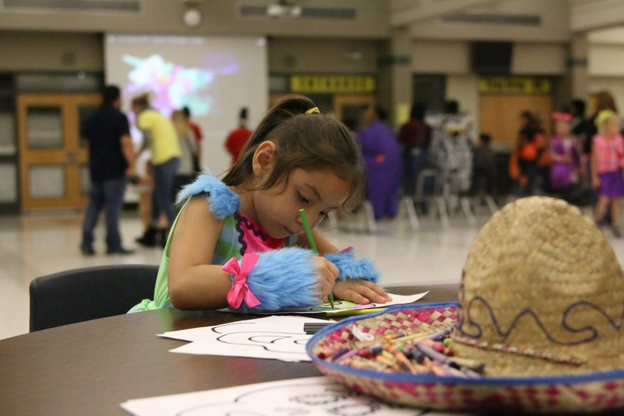 A little girl coloring a skull at the Spanish Club station.
